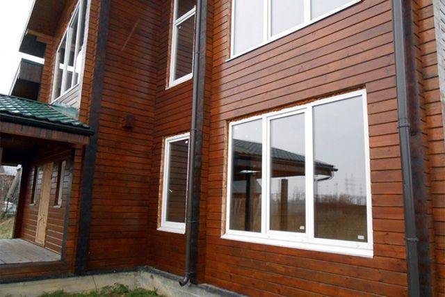 Белый пластик окон хорошо вписался в экстерьер дома. Торцы бруса прошли дополнительную обработку.