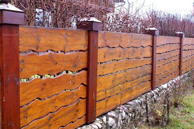 Одно из возможных решений – сплошной забор из необрезной доски.